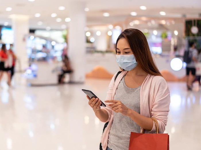 Young asian woman wearing surgical mask shopping in clothes store at the mall, New normal and lifestyle concept