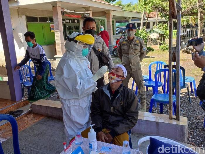 Puluhan warga Desa Tigasan Wetan, Kecamatan Leces, Kabupaten Probolinggo merebut jenazah COVID-19 saat pemakaman dengan prokes. Hari ini mereka menjalani swab PCR.