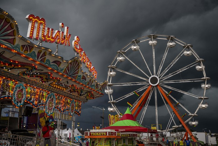 Storm clouds loom over the Miller Spectacular Shows Midway at the Illinois State Fairgrounds in Springfield, Ill., Thursday, Aug. 12, 2021. (Justin L. Fowler/The State Journal-Register via AP)