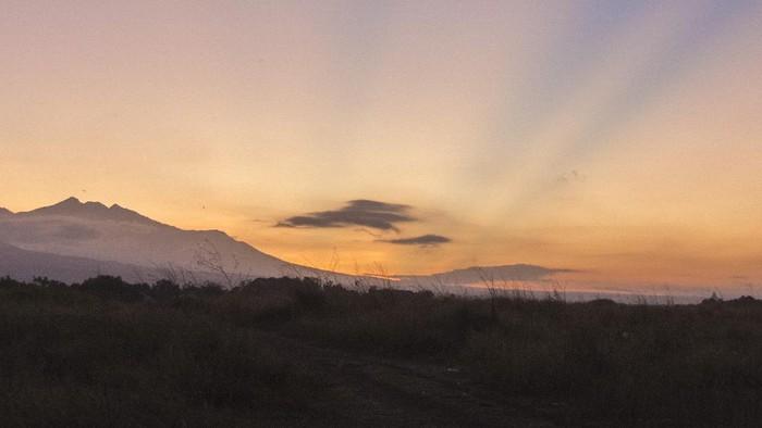 Siluet puncak Gunung Rinjani terlihat jelas saat matahari terbit dari Kota Mataram, NTB, Sabtu (14/8/2021). Gunung Rinjani yang terletak di bagian utara Pulau Lombok merupakan gunung berapi tertinggi kedua di Indonesia dengan ketinggian 3,726 mdpl dan menjadi salah satu tempat wisata pegunungan favorit di NTB. ANTARA FOTO/Ahmad Subaidi/rwa.
