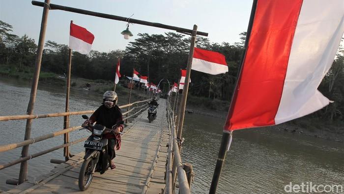 Jembatan bambu di Kulon Progo tampak dihiasi puluhan bendera Merah Putih. Hal itu dilakukan dalam rangka menyambut HUT RI ke-76 pada 17 Agustus 2021 mendatang.