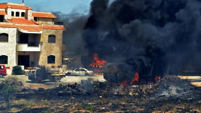 Vehicles burn outside the reported home of the lot owner, where the exploded fuel tank was placed, in the village of Tlel in Lebanons northern region of Akkar on August 15, 2021. - At least 20 people were killed and nearly 80 others injured when a fuel tank exploded in Lebanons northern region of Akkar, the Red Cross and state media said. The official National News Agency said the explosion took place following scuffles between