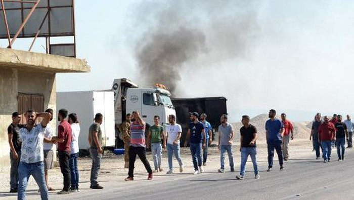 A picture taken on August 15, 2021, shows people gathering at the site of a fuel tank explosion in the village of Tlel in Lebanons northern region of Akkar. - At least 20 people were killed and nearly 80 others injured when a fuel tank exploded in Lebanons northern region of Akkar, the Red Cross and state media said. The official National News Agency said the explosion took place following scuffles between