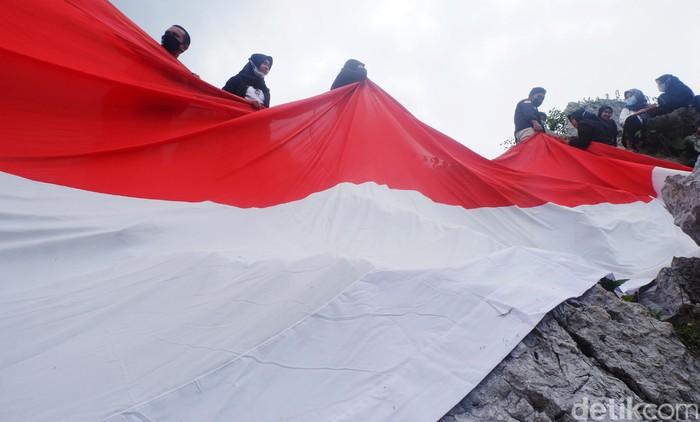 Para pecinta alam membentangkan bendera merah putih raksasa di puncak bukit Karang Gumantung, Banjarnegara, Jawa Tengah. Pengibaran bendera ini dalam rangka menyambut HUT ke-76 RI.