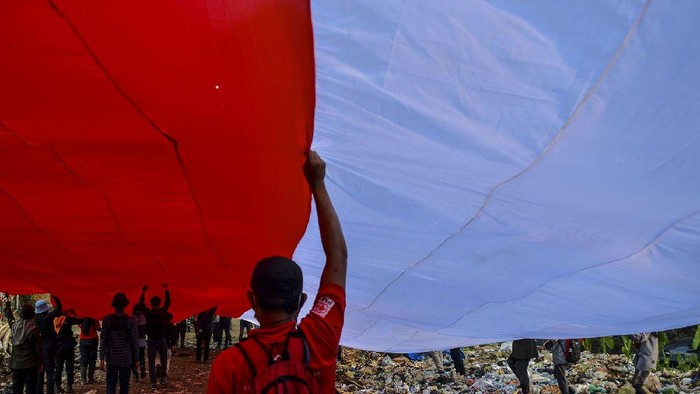 Sejumlah pegiat lingkungan yang tergabung dalam komunitas Republik Aer membentangkan bendera merah putih di Tempat Pembuangan Akhir Sampah (TPAS) Cianggir, Kota Tasikmalaya, Jawa Barat, Minggu (15/8/2021). Pembentangan bendera merah putih raksasa di TPAS tersebut dilakukan dalam rangkaian acara menyambut peringatan HUT Kemerdekaan ke-76 RI, sekaligus mengampanyekan kepedulian terhadap lingkungan dan menjaga ekosistem di masa pandemi COVID-19 serta memupuk rasa nasionalisme. ANTARA FOTO/Adeng Bustomi/wsj.
