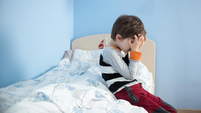 Sad, upset little boy sitting on the edge of his bed. Covering his face with hands.
