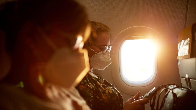 Side view with focus on background of mature Caucasian mother and teenage daughter wearing protective masks as they travel by airplane in time of COVID-19.