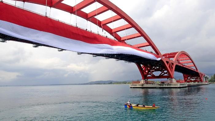 Nelayan melintasi Jembatan Youtefa yang dipasang  bendera Merah Putih di Jayapura, Papua, Selasa (17/8/2021). Pemasangan bendera Merah Putih sepanjang 400 meter tersebut guna memeriahkan HUT ke-76 RI. ANTARA FOTO/Gusti Tanati/wpa/aww.