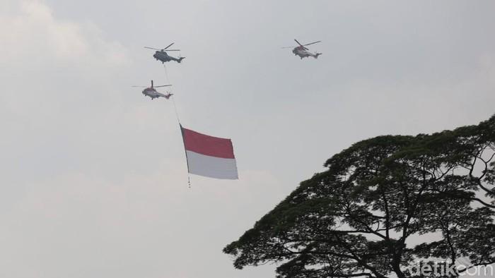 Bendera Merah Putih berukuran raksasa menghiasi langit Jakarta. Bendera itu dibawa oleh pesawat tempur dan helikopter di tengah perayaan HUT ke-76 RI.