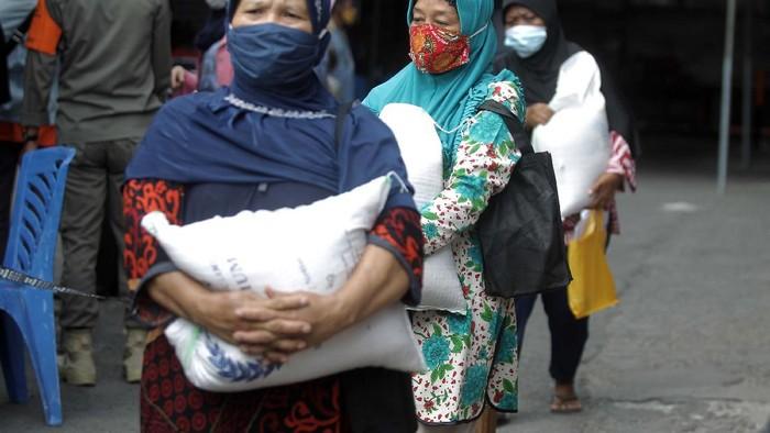 Pembagian BST berupa beras 10 kilogram dilakukan di Kantor Pos Besar, Yogyakarta, Selasa (17/8/2021). Warga tampak mengantre dengan mengabaikan protokol kesehatan.