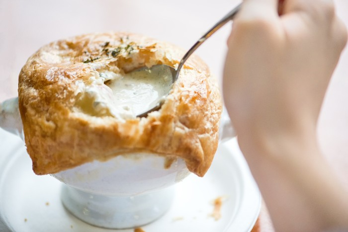 Personal perspective of a girl holding a spoonful of savoury filling from a pot pie with puff pastry crust in a restaurant.