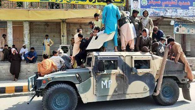 Los combatientes talibanes y los residentes locales se sientan en un vehículo Humvee del Ejército Nacional Afgano (ANA) al costado de la carretera en la provincia de Laghman el 15 de agosto de 2021.  (Foto - / AFP)