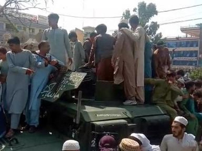 Taliban fighters and local residents sit on an Afghan National Army (ANA) Humvee vehicle along the roadside in Laghman province on August 15, 2021. (Photo by - / AFP)