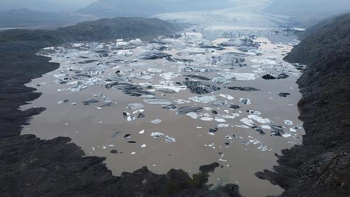HOFN, HORNAFJORDUR, ICELAND - AUGUST 17: In this aerial view Hoffellsjokull glacier lies behind moraines and an iceberg-filled lagoon the glacier once covered on August 17, 2021 near Hofn, Iceland. Iceland is feeling a strong impact from global warming. Since the 1990s 90% of Iceland's glaciers have been retreating and projections for the future show a continued and strong reduction in size of its five ice caps. Flaajokull is one of dozens of glacier tongues that descend from Vatnajokull, Iceland's biggest ice cap.  (Photo by Sean Gallup/Getty Images)