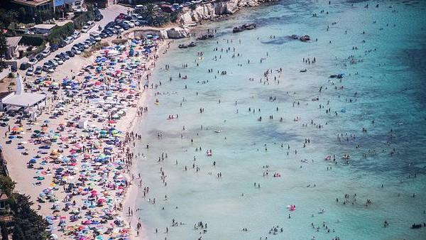 Wisatawan memadati pantai Fontane Bianche dalam pemandangan udara dari helikopter Penjaga Pantai di Siracusa, Italia.