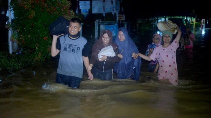 Warga melakukan evakuasi mandiri ke tempat yang lebih tinggi, akibat banjir merendam rumah mereka, di Lubuk Buaya, Padang, Sumatera Barat, Rabu (18/8/2021). Intensitas hujan tinggi sejak Rabu siang membuat air sungai meluap dan merendam pemukiman di kota itu.  ANTARA FOTO/Iggoy el Fitra/hp.