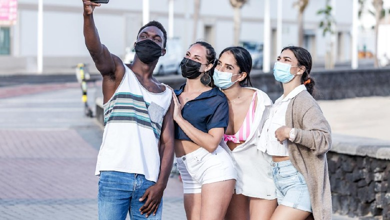 Group of smiling multiracial friends wearing masks standing in city and taking selfie on smartphone while spending time together in summer on Lanzarote