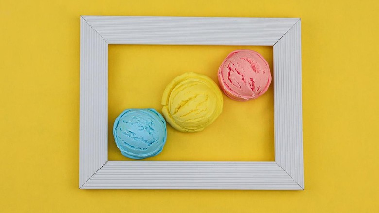 Homemade fruit ice cream in a white wooden frame on a yellow background, top view close-up.