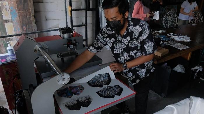 Perajin menunjukkan desain masker bergambar burung Garuda yang sempat viral di media sosial setelah masker dengan gambar yang sama digunakan oleh artis Cinta Laura di Kitasatubali, Badung, Bali, Jumat (20/8/2021). Desain masker kain yang menampilkan gambar dari karya lukisan para seniman lokal Bali, Yogyakarta, Badung, dan Jakarta dengan teknik printing tersebut menembus pasar ekspor di sejumlah negara dengan harga jual Rp45.000 - Rp125.000 per set. ANTARA FOTO/Nyoman Hendra Wibowo/hp.
