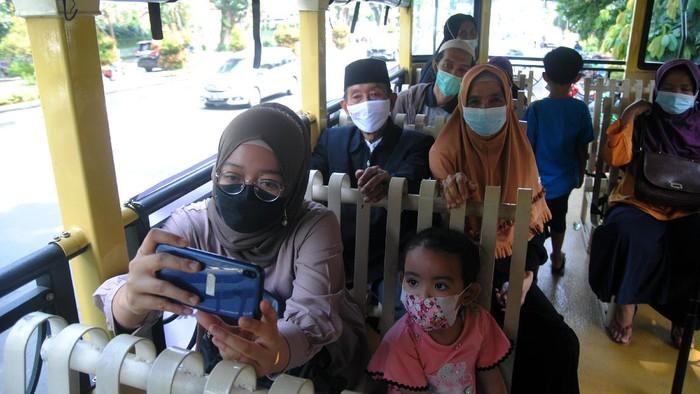 Sejumlah warga naik bus Uncal usai mengikuti vaksinasi COVID-19 massal di Puri Begawan, Baranangsiang, Kota Bogor, Jawa Barat, Jumat (20/8/2021). Satgas Penanganan COVID-19 Kota Bogor menggunakan layanan bus Uncal untuk antar jemput warga menuju sentra vaksinasi COVID-19 sebagai upaya mempercepat program vaksinasi yang dilakukan pemerintah. ANTARA FOTO/Arif Firmansyah/hp.