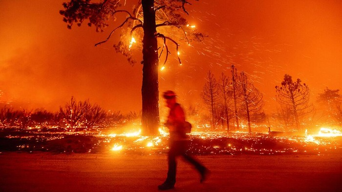 In this long exposure photo, embers light up hillsides as the Dixie Fire burns near Milford in Lassen County, Calif., on Tuesday, Aug. 17, 2021. (AP Photo/Noah Berger)