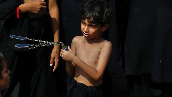 Anak-anak juga tidak mau ketinggalan dalam peringatan itu. AP/Arshad Butt