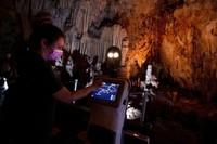 Persephone memandu para pengunjung di dalam gua Alistrati, sekitar 135 kilometer (84 mil) timur laut Thessaloniki, Yunani, Senin, 2 Agustus 2021. Persephone, yang disebut-sebut sebagai robot pertama di dunia yang digunakan sebagai pemandu wisata di dalam gua, telah menyambut pengunjung ke gua Alistrati, sejak pertengahan Juli. (AP Photo/Giannis Papanikos)