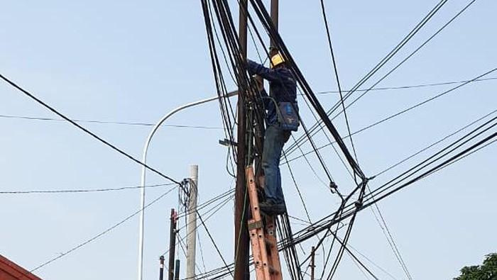 Petugas memindahkan kabel dari tiang-tiang di Jl Erha dan Jl Cinere Raya. (Dok Istimewa)