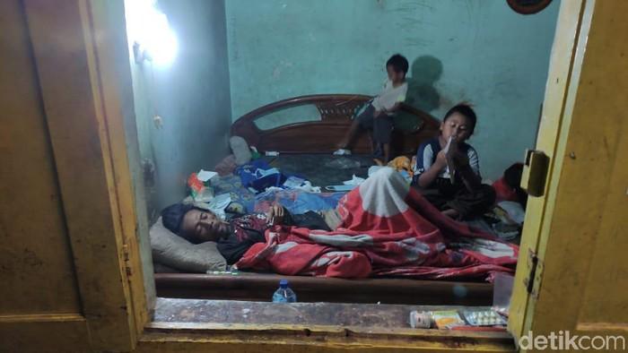 Potret mengarukan tampak dari jendela sebuah rumah di Kota Malang. Tampak dua bocah tengah merawat sang ayah yang terbaring lumpuh.