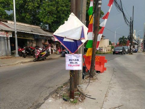 Telkom menandai tiang-tiang di badan Jl Erha Depok, menyatakan bahwa tiang-tiang ini bukan miliknya. (Dok Telkom)