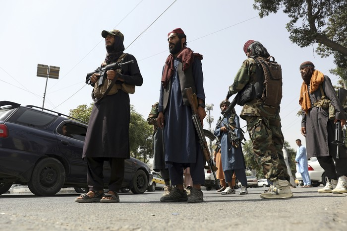 Taliban fighters patrol as two Traffic policemen stand, left, in Kabul, Afghanistan, Thursday, Aug. 19, 2021. The Taliban celebrated Afghanistans Independence Day on Thursday by declaring they beat the United States, but challenges to their rule ranging from running a country severely short on cash and bureaucrats to potentially facing an armed opposition began to emerge. (AP Photo/Rahmat Gul)