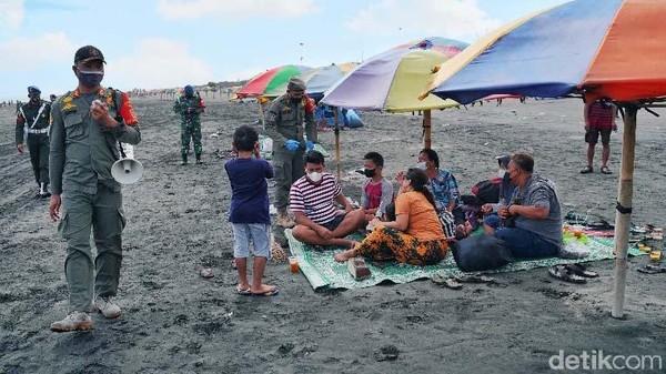 Satpol PP dan TNI-Polri mengingatkan warga untuk tidak berkumpul dan tetap menjaga Prokes.