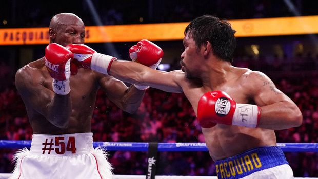 Yordenis Ugas, right, of Cuba, hits Manny Pacquiao, of the Philippines, in a welterweight championship boxing match Saturday, Aug. 21, 2021, in Las Vegas. (AP Photo/John Locher)