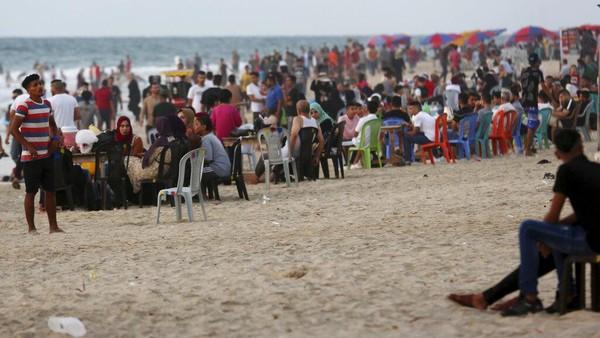 Ada juga warga yang membawa payung untuk berteduh di tepi pantai.