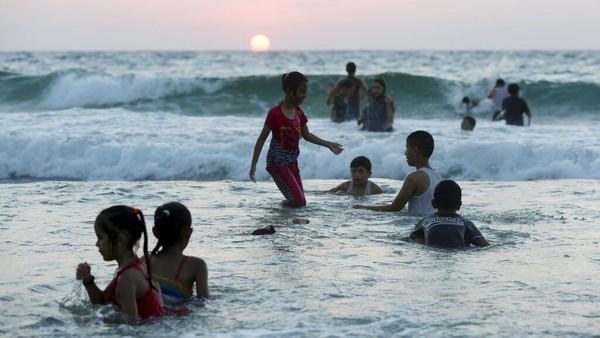 Para warga memilih pantai untuk mendinginkan diri dengan air laut.