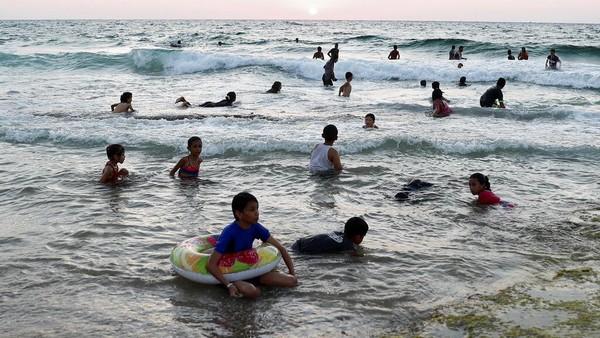 Warga Palestina duduk menikmati pantai kamp pengungsi Deir el-Balah di Laut Mediterania, Jalur Gaza tengah.
