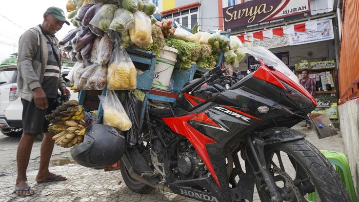 Pedagang sayur keliling Budi (63) berjualan di depan emperan toko, Entrop, Kota Jayapura, Papua, Minggu (22/8/2021). Budi sehari-hari beraktivitas sebagai pedagang sayur keliling gunakan motor sport Honda CBR 6 speed dengan harga puluhan juta rupiah. ANTARA FOTO/Indrayadi TH/foc.
