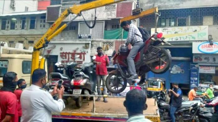 Pengendara motor nekat tetap berada di motor meski sedang diangkut crane