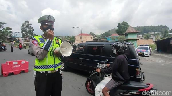 Petugas kepolisian tak henti-hentinya mengimbau agar wisatawan untuk putar balik karena masih PPKM. Bagi pengendara yang terindikasi hendak berwisata, langsung diperintahkan untuk memutar balik kendaraannya. (Andika Tarmy/detikTravel)