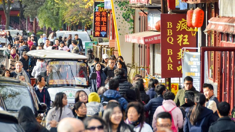 Beijing, China - November 19, 2016: Typical crowded hutong street in Beijing, China. Photo taken during the day and contains many people.