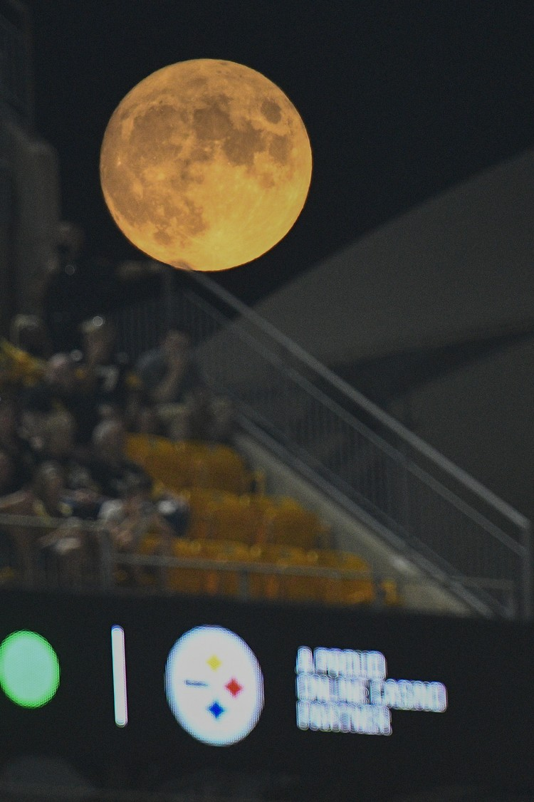 A full moon rises as fans watch the second half of an NFL preseason football game between the Pittsburgh Steelers and the Detroit Lions, Saturday, Aug. 21, 2021, in Pittsburgh. (AP Photo/Don Wright)