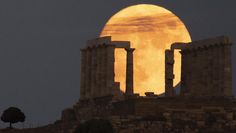 The sturgeon full moon rises behind the ancient Greek marble temple of Poseidon at Cape Sounion, about 70 Km (45 miles) south of Athens, Saturday, Aug. 21, 2021. On Sunday, more than a hundred archeological sites and museums across the country will welcome the public to admire the full moon. (AP Photo/Michael Varaklas)