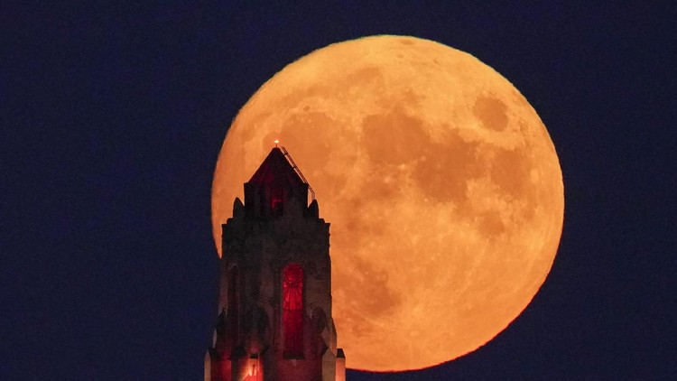 The Art Deco spire of the Kansas City Power and Light building stands against the full moon as it rises beyond the downtown skyline Saturday, Aug. 21, 2021, in Kansas City, Mo. The August full moon is known as the sturgeon moon. (AP Photo/Charlie Riedel)