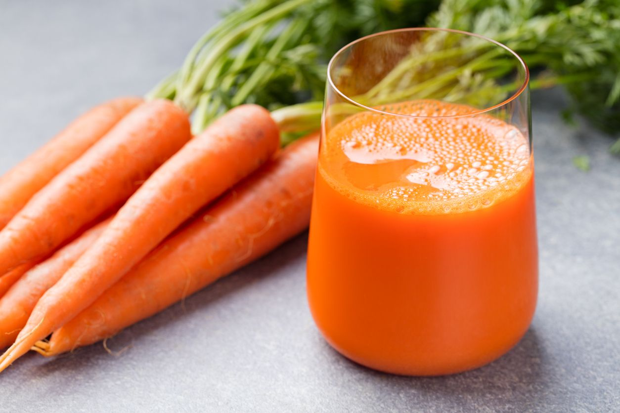 Nước ép cà rốt trong ly và cà rốt tươi Thức ăn lành mạnh trên nền đá xám.