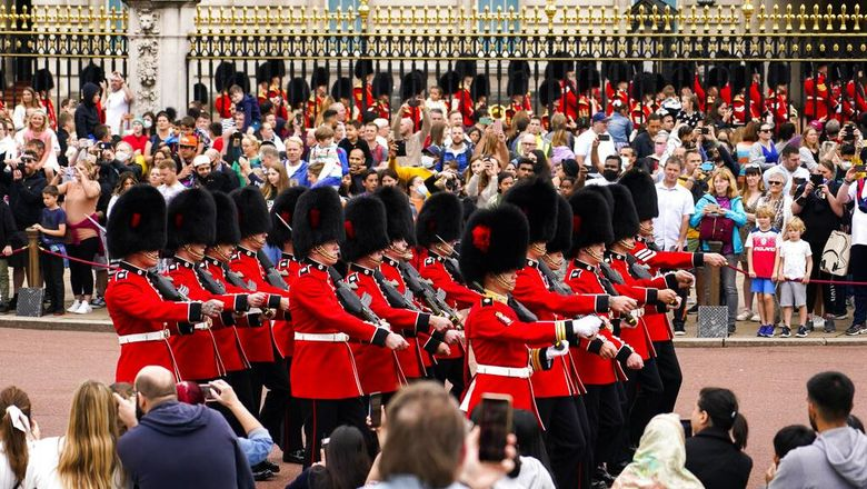 Members of the public watch the Changing of the Guard ceremony at Buckingham Palace, London, Monday August 23, 2021, which is taking place for the first time since the start of the coronavirus pandemic. (AP Photo/Alberto Pezzali)