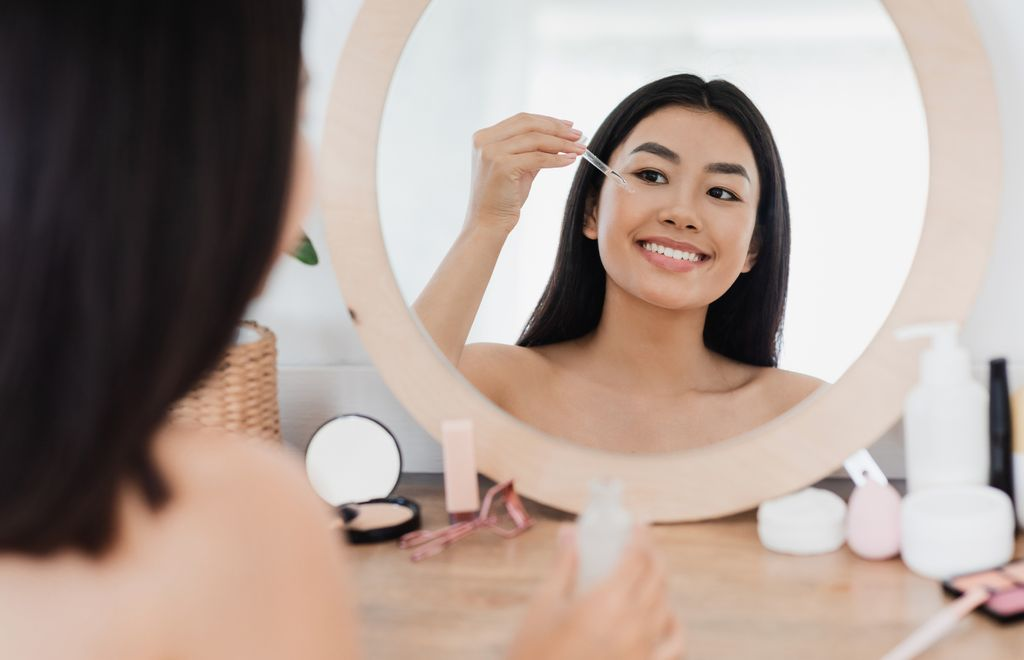 Eye zone care concept. Happy beautiful asian girl applying eye serum in front of mirror at home