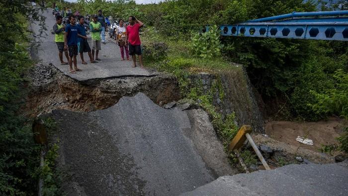 Sejumlah warga meratakan tebing sungai untuk membuat jalan alternatif setelah jembatan ambruk digerus arus sungai di Desa Pombewe, Sigi, Sulawesi Tengah, Rabu (25/8/2021). Jembatan yang menghubungkan ruas jalan Palu-Sigi itu ambruk setelah digerus arus air sungai akibat hujan deras di hulu. Tidak ada korban jiwa dalam peristiwa itu namun arus lalulintas terputus dan dialihkan ke jalan alternatif lainnya sejauh lebih dari 20 kilometer. ANTARA FOTO/Basri Marzuki/hp.