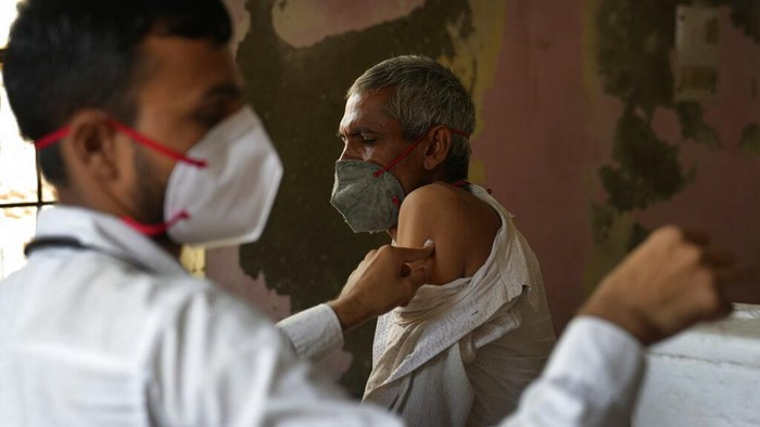 A health worker administers the vaccine for COVID-19 in New Delhi, India, Tuesday, Aug. 24, 2021. (AP Photo/Manish Swarup)