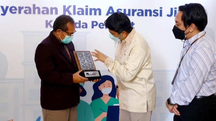 Direktur AXA Mandiri Uke Giri Utama menyaksikan penyerahan secara secara simbolis klaim untuk tenaga kesehatan dari perwakilan keluarga perawat, yang disaksikan juga oleh Ketua Umum DPP Persatuan Perawat Nasional Indonesia (PPNI) Harif Fadillah, di Jakarta, Kamis (26/8/2021). PT AXA Mandiri Financial Services (AXA Mandiri) dan PT Bank Mandiri (Persero) Tbk (Bank Mandiri) menyerahkan klaim tahap pertama sebesar Rp 4,25 Miliar kepada 170 tenaga kesehatan yang gugur saat menangani COVID-19.