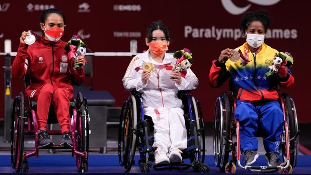 TOKYO, JAPAN - AUGUST 26: Silver medalist Ni Nengah Widiasih of Team Indonesia, Gold medalist Guo Lingling, and Bronze medalist Clara Fuentes of Team Venezuela pose for a photo after the women's -41kg powerlifting final on day 2 of the Tokyo 2020 Paralympic Games at on August 26, 2021 in Tokyo, Japan. (Photo by Christopher Jue/Getty Images for International Paralympic Committee)